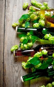Birra e luppolo verde su un tavolo di legno.