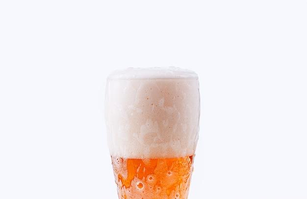 La birra viene versata in un bicchiere su uno sfondo bianco