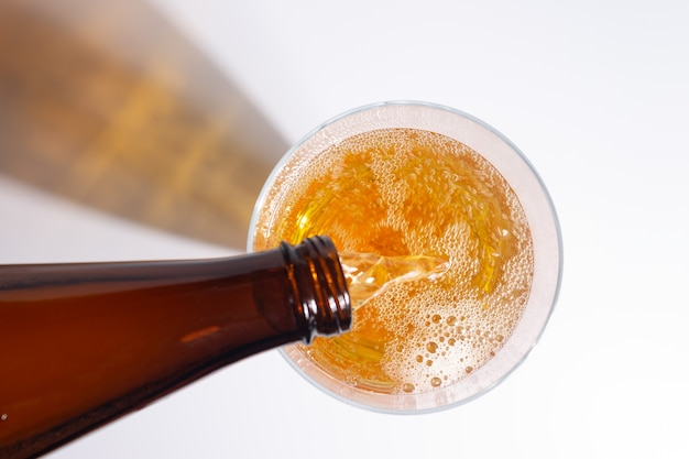 La birra sta versando dalla bottiglia nel bicchiere