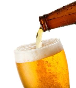 La birra sta versando nel vetro isolato