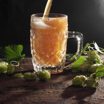 La birra sta versando in una tazza di vetro, sfondo nero e piante di luppolo nelle vicinanze.