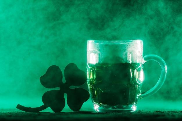 Boccale di birra con birra verde e shamrock in un fumo.