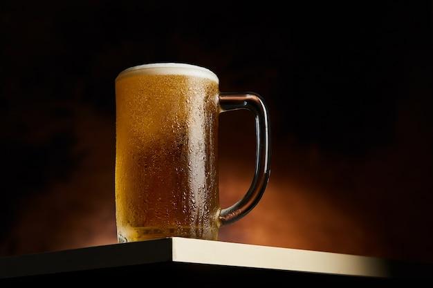 Birra in tazza sulla tavola di legno