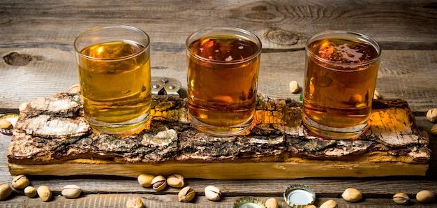 Festa della birra. tre birre su bancarella di betulla con pistacchi intorno.