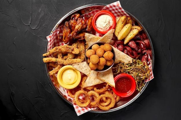 Il piatto di birra con alette di pollo piccanti anelli di calamari patatine fritte anelli di cipolla polpette di formaggio tartare di pane...