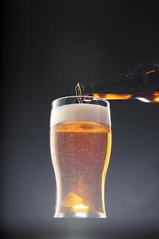 Birra che versa nel vetro su fondo nero