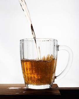 Birra che versa nel vetro isolato