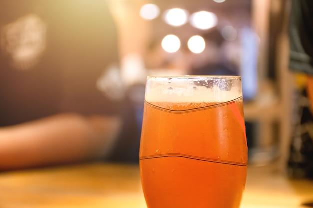 Birra nel bicchiere corto sul tavolo al bar notturno con sfondo persone che si incontrano nel club.
