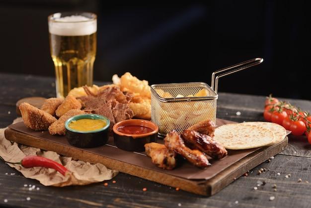 Snack alla birra. ali di pollo fritto, patatine fritte, anelli di cipolla, formaggio in pastella e carne secca. su una tavola di legno