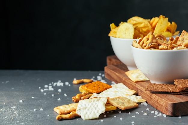 Snack birra sul tavolo di pietra. vari cracker, patatine fritte. vista dall'alto