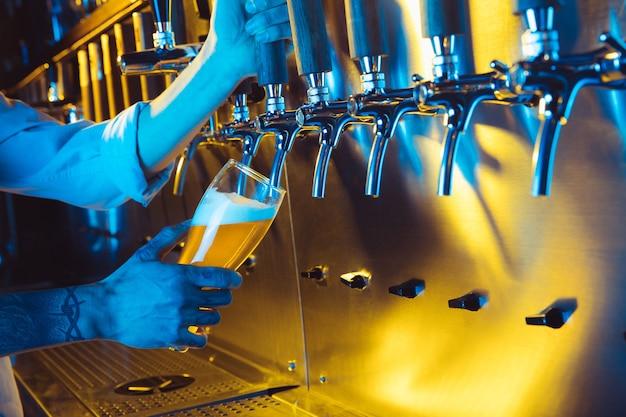La birra alla spina in un pub. nessuno. messa a fuoco selettiva. concetto di alcol. stile vintage. birra artigianale. tavolo da bar. rubinetti in acciaio. rubinetti lucidi. bicchiere di birra. concetto dell'oktoberfest