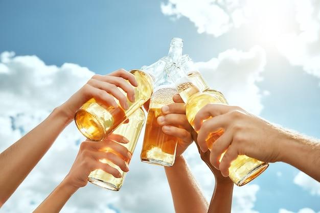 L'immagine ritagliata del tempo della birra delle mani sta tintinnando bottiglie di birra sullo sfondo del cielo estivo