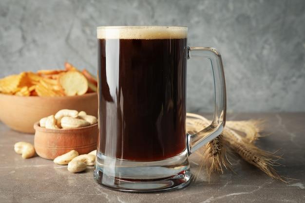 Birra, grano e snack sulla tavola grigia, primi piani