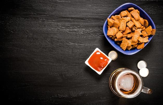 Birra con cracker e ketchup su una lavagna. spazio per il testo libero. vista dall'alto