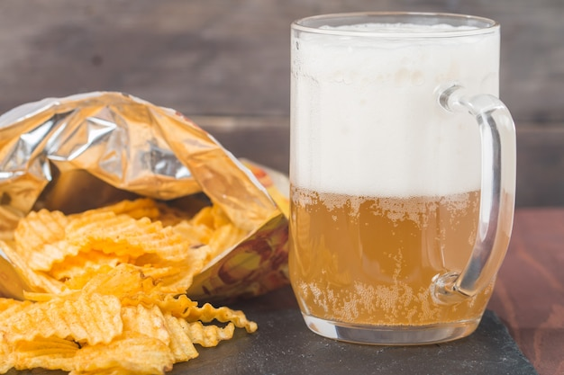 Birra con schiuma in tazza di vetro e patatine in sacchetto
