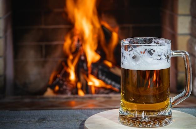 Birra con schiuma nella tazza, sul tavolo di legno, contro un accogliente caminetto