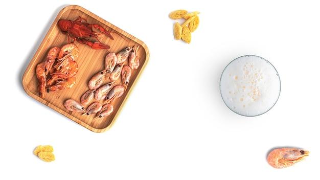 Birra con spuntini di pesce su uno sfondo bianco. foto di alta qualità