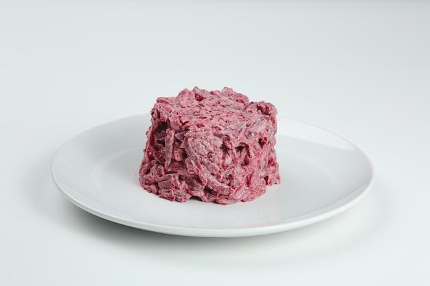 Insalata di maionese di barbabietola e aglio sul piatto bianco. insalata di barbabietola isolato su sfondo bianco.