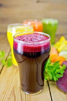Succo di barbabietola in primo piano e succo di carota, zucca e cetriolo in un bicchiere alto, verdure su uno sfondo di assi di legno