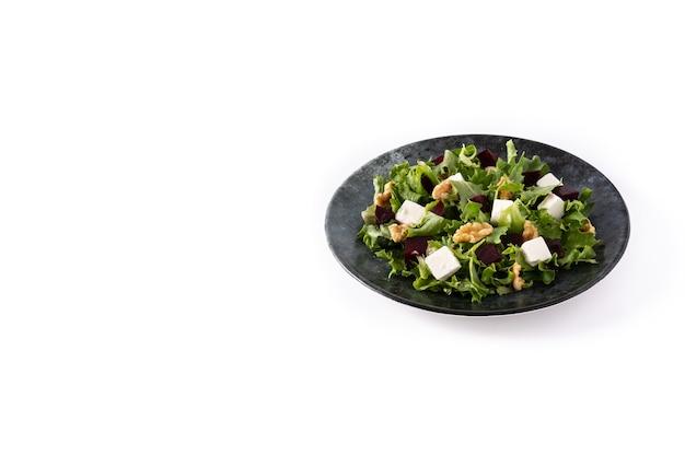 Insalata di barbabietole con feta, lattuga e noci isolate su sfondo bianco