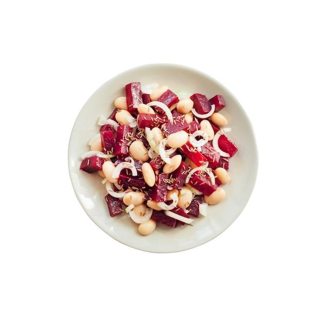 Insalata di barbabietole con fagioli bianchi, sottaceti e cipolla, condita con olio e aromatizzata con semi di cumino