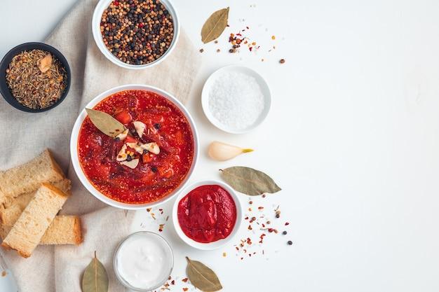 Zuppa di barbabietole con aglio, pane e spezie su uno sfondo bianco. concetto di cucina.