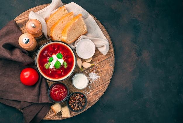 Zuppa di barbabietole con panna acida e basilico, pane, pomodoro e salsa di pomodoro su una tavola rotonda di legno su uno sfondo marrone di cemento. vista laterale.