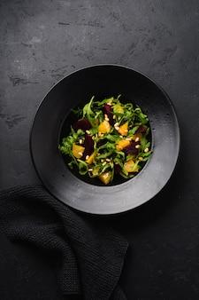 Insalata di barbabietole, arance, pinoli, olio d'oliva, feta e rucola in piatto di ceramica nera su fondo di cemento scuro.