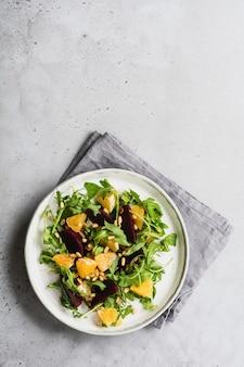 Barbabietole, arancia, pinoli, olio d'oliva, formaggio feta e insalata di rucola nel piatto di ceramica sulla vecchia superficie del tavolo di cemento