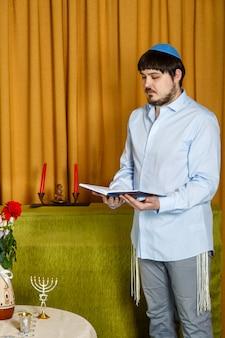 Prima della cerimonia della chuppah, lo sposo ebreo legge le preghiere siddur nella sinagoga. foto verticale