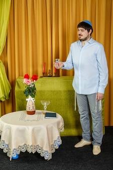 Prima della cerimonia della chuppah, lo sposo ebreo nella sinagoga tiene un bicchiere kiddush con vino. foto verticale