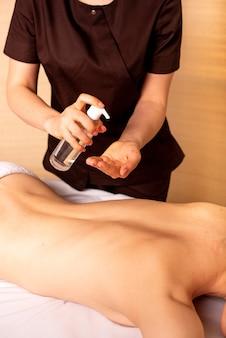 Prima del massaggio, la massaggiatrice applica un olio spray sulle mani