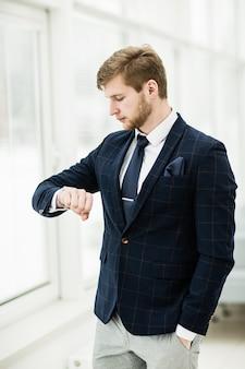 Uomo d'affari principiante guarda l'orologio.