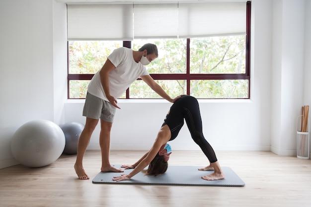 Yogi principiante e il suo allenatore praticano yoga indossando una maschera protettiva durante il covid-19