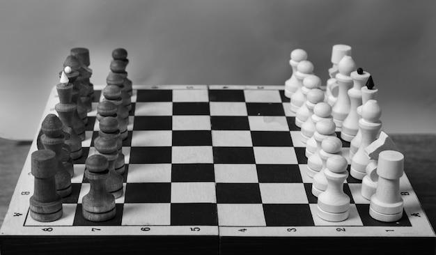 L'inizio di una partita a scacchi, pezzi di fila, primo piano, messa a fuoco selettiva, bianco e nero