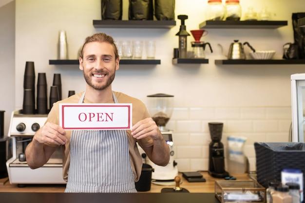 Inizio del lavoro. felice giovane uomo barbuto in piedi vicino a bar con cartello davanti a lui dicendo che il caffè è aperto
