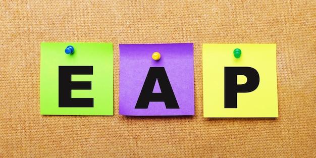 Su fondo beige, adesivi multicolori per appunti con la parola eap employee assistance program