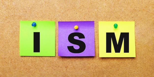 Su fondo beige, adesivi multicolori per appunti con la parola ism