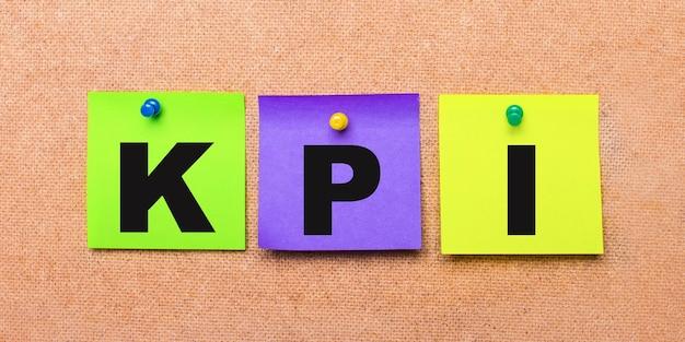 Su fondo beige, adesivi multicolori per appunti con la parola kpi