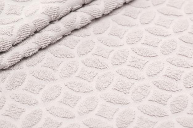 Asciugamano da bagno beige con pieghe. sfondo di tessuto strutturato