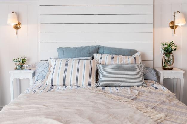 Coperta beige su letto king-size e cactus in vasi d'oro sull'armadio in camera da letto spaziosa. letto king-size con testiera morbida e biancheria da letto rosa pastello. coperta di pastello sul letto nell'interno della camera da letto