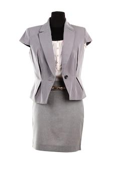 Camicetta beige, giacca grigia e gonna grigia su manichino, isolato su bianco