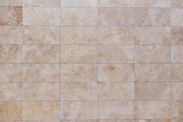 Muro di cemento beige. mattonelle di struttura dell'arenaria