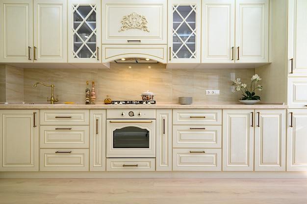 Interiore della cucina classica contemporanea beige progettato in stile provenzale, vista frontale sulla facciata