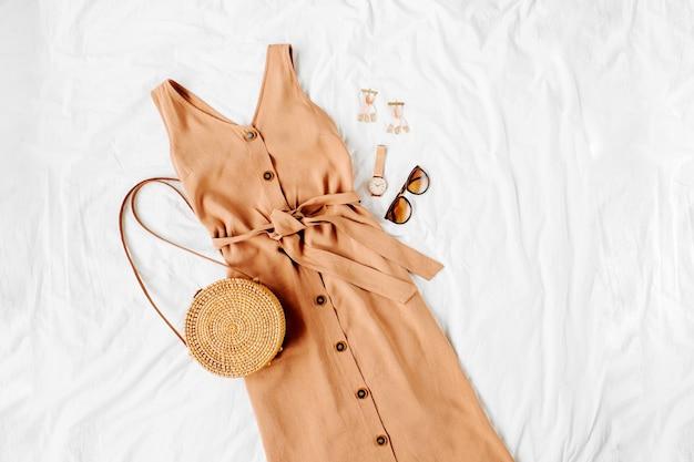 Abito beige con borsa in bambù e accessori su letto bianco. elegante outfit da donna autunnale o estivo. vestiti alla moda. disposizione piana, vista dall'alto.