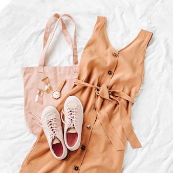 Abito beige con eco bag, sneakers e accessori su letto bianco. elegante outfit da donna autunnale o estivo. vestiti alla moda. disposizione piana, vista dall'alto.