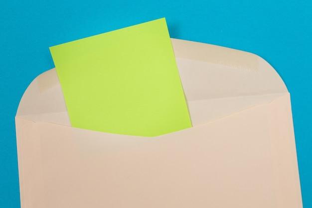 Busta beige con foglio di carta verde vuoto all'interno