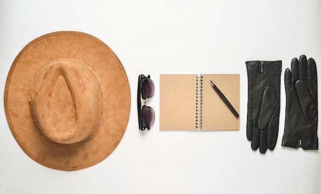 Cappello di feltro beige, taccuino con penna, occhiali da sole, guanti su sfondo bianco