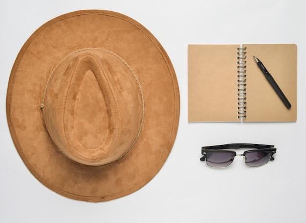 Cappello di feltro beige, taccuino con penna, occhiali da sole su sfondo bianco