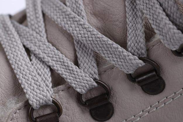 Lacci beige con rivetti in metallo sugli stivali. metodi di allacciatura sul concetto di scarpe